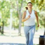portrait of a mid adult woman jogging in a park --- Image by © Royalty-Free/Corbis